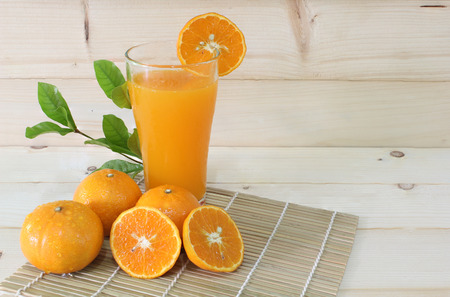 Fresh oranges and oranges juice in glass with pieces oranges on the wooden plank. Still Life image and select focus, space for messages. Stock fotó