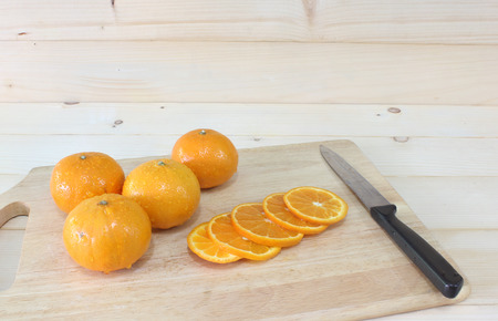Fresh Oranges slice on a wooden cutting board and knife. Still Life image and select focus, space for messages.
