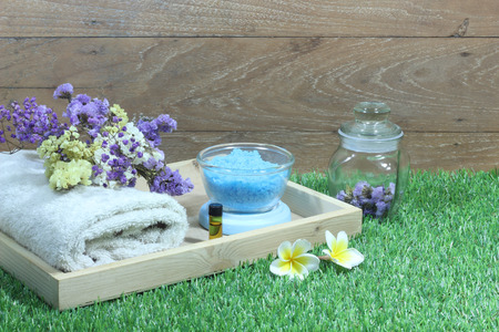 Set aromatherapy spa and candle with flowers on artificial grass.