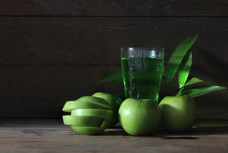 Apple juice with many green apples with drops of water, leaves on the old wooden table.