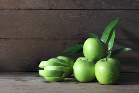 Many green apples with drops of water, leaves on the old wooden table. Stock fotó