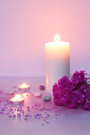 Candlelight and pink flowers on pink background, romantic feelings.