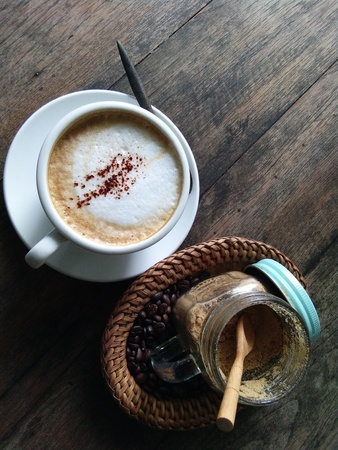Cappuccino with coffee beans and sugar cane powder in a basket on the old wooden desk as background.