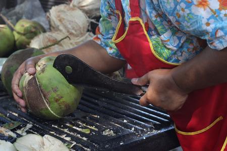 Woman is using a peeling coconut knife.