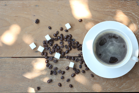 Hot coffee on old wooden floors with coffee beans and sugar cubes, on top view.