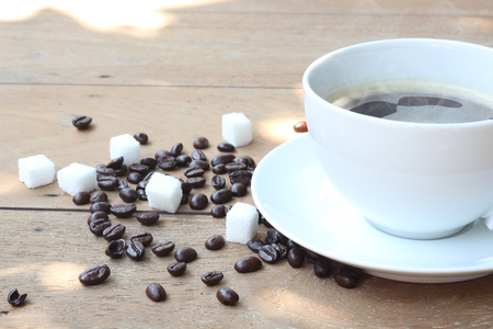 Hot coffee on old wooden floors with coffee beans and sugar cubes.