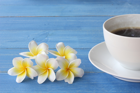 Hot coffee on a blue wooden floor With frangipani flowers. Stock fotó