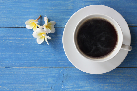 Hot coffee on a blue wooden floor With frangipani flowers, on top view. Stock fotó