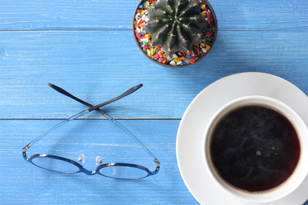 Hot coffee on a blue wooden floor with Gymnocalycium cactus and glasses, on top view. Stock fotó