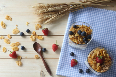 Healthy breakfast. Whole grain cereal with fresh blueberries and strawberries on rustic wooden background. Top view.