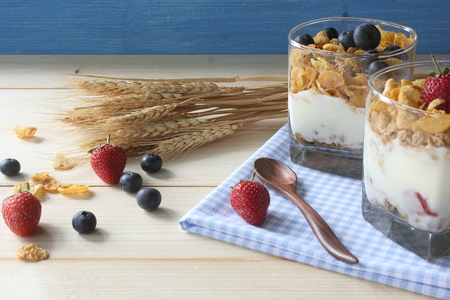 Healthy breakfast. Whole grain cereal with fresh blueberries and strawberries on rustic wooden background.