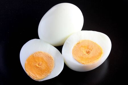 Boiled eggs and  half on a black background