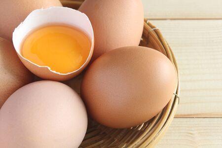 Fresh eggs and yolk in shells in basket.