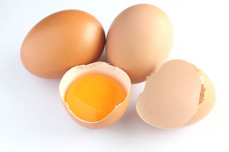 Fresh eggs and yolk in shells on white background.