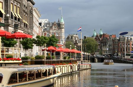 Tour boats in a canal outside a restaurant in Amsterdam Stock Photo - 3295690