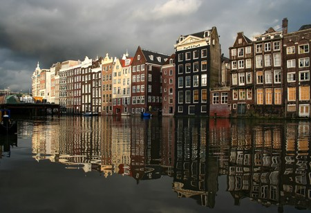 Amsterdam canal with historic houses, rain clouds and reflections