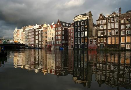 Amsterdamse gracht met historische huizen, regen wolken en reflecties