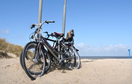 child seat: Three bicycles with child seat parked on the beach Stock Photo