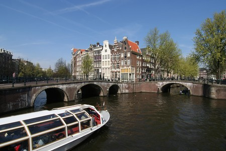 house gables: Tour boat in an Amsterdam canal