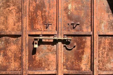 Padlock on an old rusty iron door photo