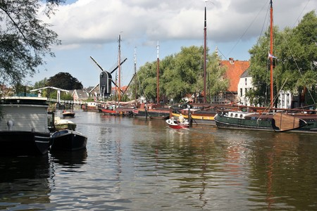 Old an new boats on a canal in Leiden, Holland. In the distance a draw bridge and a windmill photo