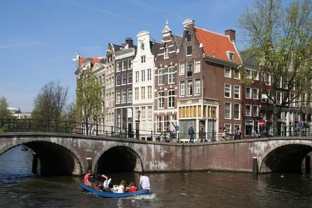 house gables: La gente en bote en un canal de Amsterdam Foto de archivo