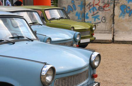 Oost-Duitse auto's geparkeerd nabij een stuk van de Berlijnse muur