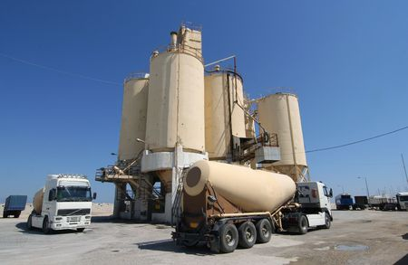 Cement factory with silos and trucks photo