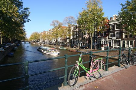 Bicycle on a bridge and touring boat in Amsterdam canal