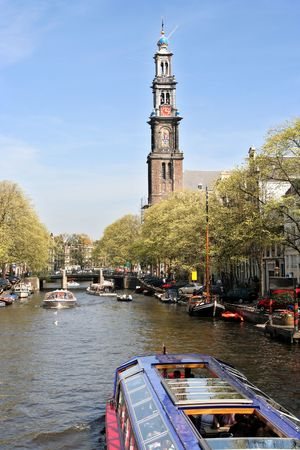 tour boats: Amsterdam canal with tour boats and the tower of the Westerchurch in the background Stock Photo