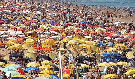 SCHEVENINGEN, HOLLAND - 18 juli 2009: Drukke strand op zonnige weekend in Scheveningen resort