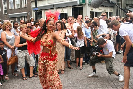 film crew: ROTTERDAM - SUMMER CARNIVAL, JULY 26, 2008. Carnival dancer being filmed by TV crew at the Caribbean Carnival in Rotterdam.