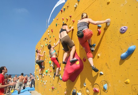 SCHEVENINGEN, HOLLAND - AUGUST 30, 2008: Annual Bouldering Competition on Scheveningen beach. Participants climbing artificial rock face.