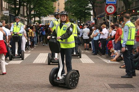 ROTTERDAM, HOLLAND - AUGUST 8, 2009: Female police officer on Segways at the Dance Parade in Rotterdam, Holland on August 8