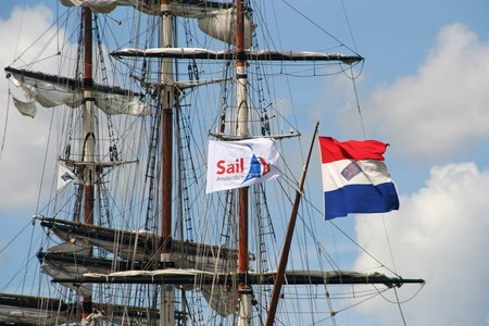 AMSTERDAM, AUGUST 19, 2010: Flag of the organisation and Dutch national flag in the mast of tall ship 'Stad Amsterdam' at Sail 2010 in Amsterdam, Holland on august 19, 2010 Stock Photo - 7659972