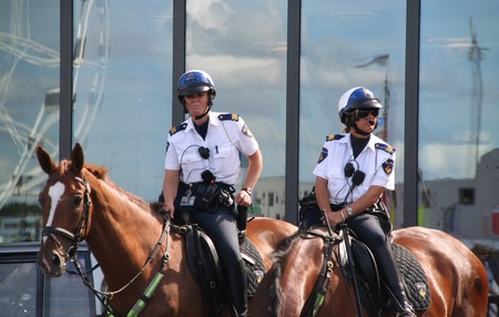 female police: AMSTERDAM, AUGUST 19, 2010: Female police officers on horseback watch the crowd at Sail 2010 in Amsterdam, Holland on august 19, 2010