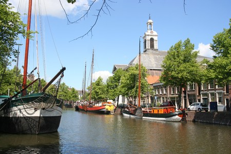 schiedam: Canal, historic boats and church in Schiedam, Holland