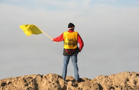 motorcross: Mariscal de bandera ondeando la bandera amarilla en la carrera de Motocross de Red Bull en Scheveningen, Holanda el 18 de noviembre de 2007