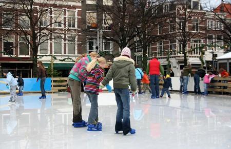 Drie meisjes schaatsen, de buitenste twee het onderwijzen van de kleinste. Foto genomen in Den Haag op 30 december 2006