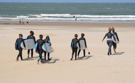 Kids with their teachers with surfboards heading for the surf at Scheveningen beach on May 19, 2007