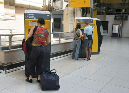 Travellers buying train tickets from a machine