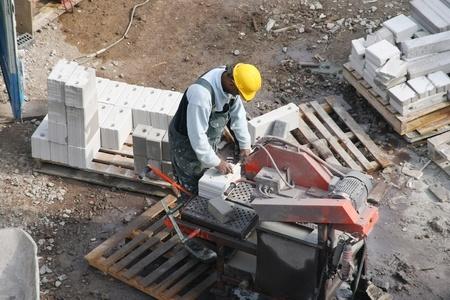 Funcionamiento de una máquina para cortar de ladrillo en un sitio de construcción el trabajador de la construcción negro. Fotografía tomada el 13 de abril de 2007 en la haya, Holanda