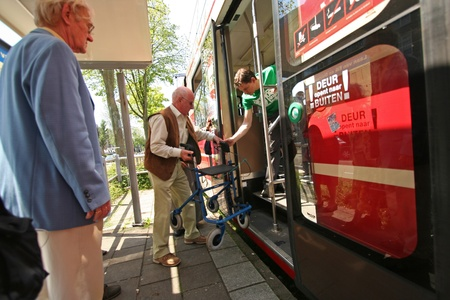 Young man assists old people with walker entering a tram on May 31, 2009 in The Hague, Holland
