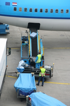 Luggage being unloaded from an airplane at the airport. Picture taken on September 25, 2009