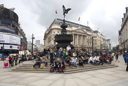 cupido: London, UK - July 21, 2011: Young people sit on the steps of the recently renovated statue of Cupido on Piccadilly Circus on July 21, 2011 in London, UK.