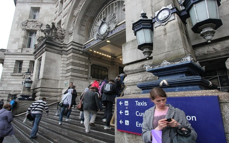 London, UK - July 21, 2011: Commuters ascend the stairs and girl using her cell phone at the entrance of Waterloo Railway station on July 21, 2011 in London, UK. Stock Photo - 11025893