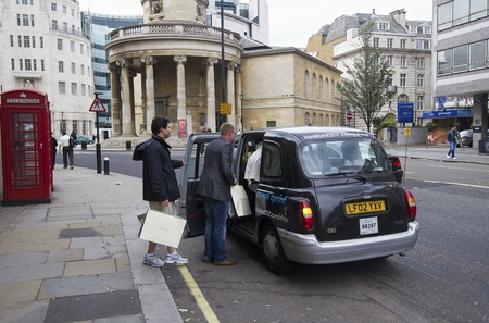London, UK - July 23, 2011: People with shopping bags take a taxi on Piccadilly in London, UK on July 23, 2011.