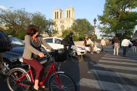 Cars and bicylists in a Paris street, Notre Dame cathedral in the background 報道画像