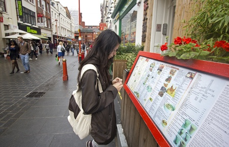 London, UK - July 21, 2011: Girl looks at the menu posted outside a Chinese restaurant in Soho Chinatown in London on July 21, 2011 in London, UK.