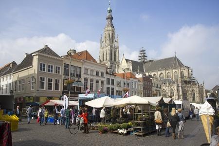 Breda, Nederland - 23 september 2011: Mensen winkelen in de markt in Breda, Nederland, met de kathedraal op de achtergrond Redactioneel